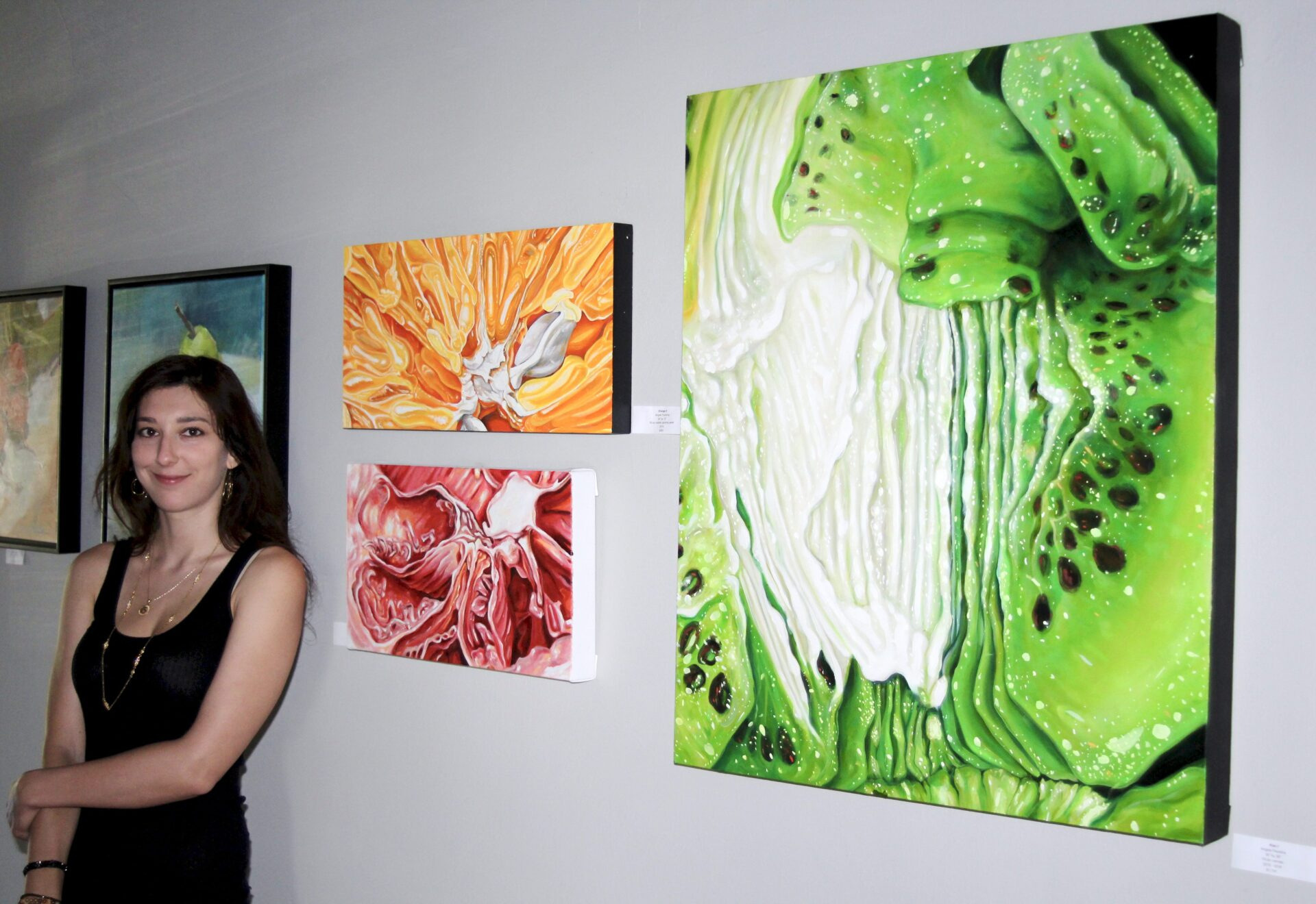 Angela Faustina and her Orange II, Pomelo I, and Kiwi I oil paintings at the From the Garden art exhibition.