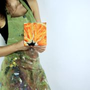 """Angela Faustina holding her oil painting Orange IV, 2017. Oil on cradled painting panel, 6"""" by 6""""."""