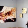 Angela Faustina and her Black Mission Fig VI, Lemon I, and Lemon II oil paintings at the From the Garden art exhibition.