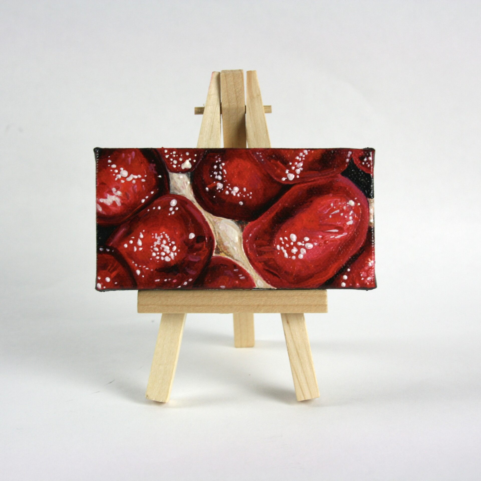 "Angela Faustina, Pomegranate XXIV, 2015. Oil on cradled painting panel with wooden easel, 4"" by 2""."