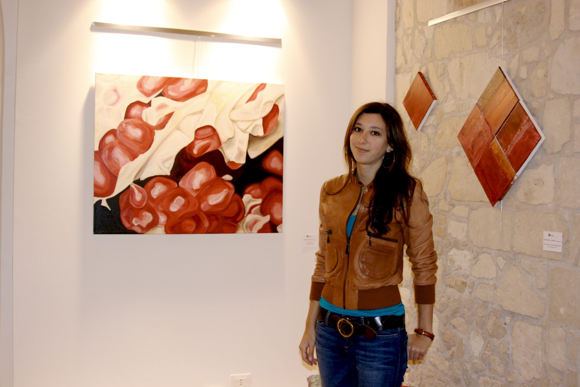 Angela Faustina with her oil painting Melagrana VIII during an art exhibition in Italy