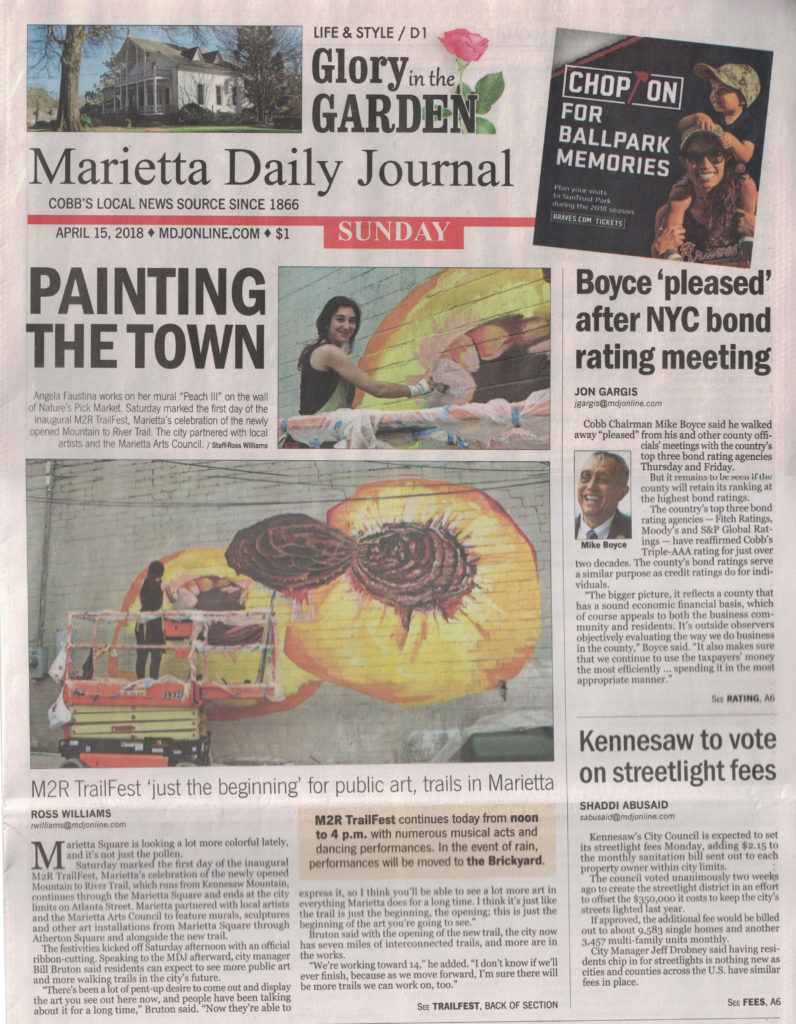Marietta Daily Journal front page news article about Angela Faustina painting Peach III mural on Marietta Square for the M2R Trailfest, sponsored by Nature's Pick Market.