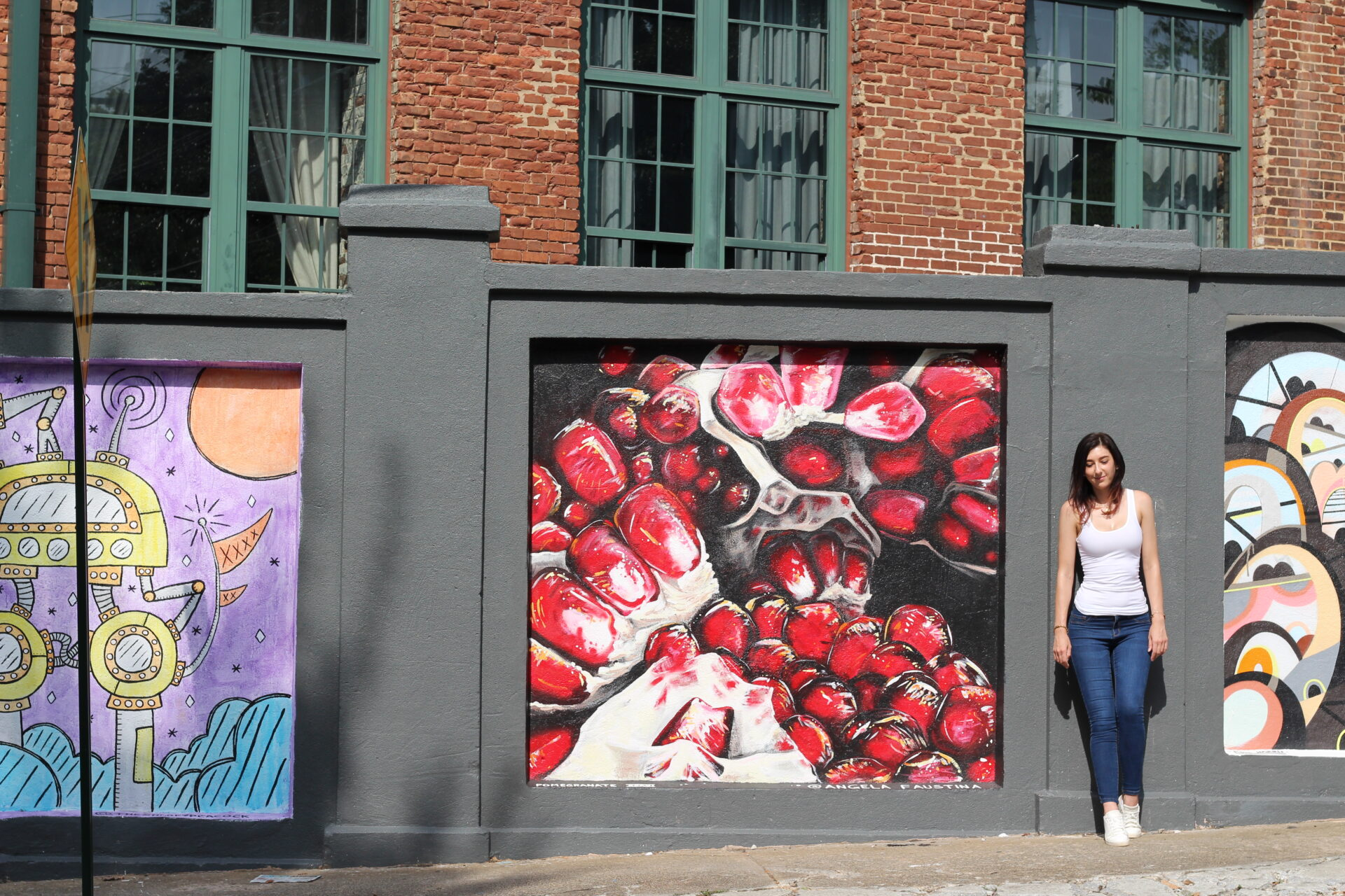 Angela Faustina with her pomegranate painting at the Stacks Squares mural public art project in Cabbagetown, Atlanta